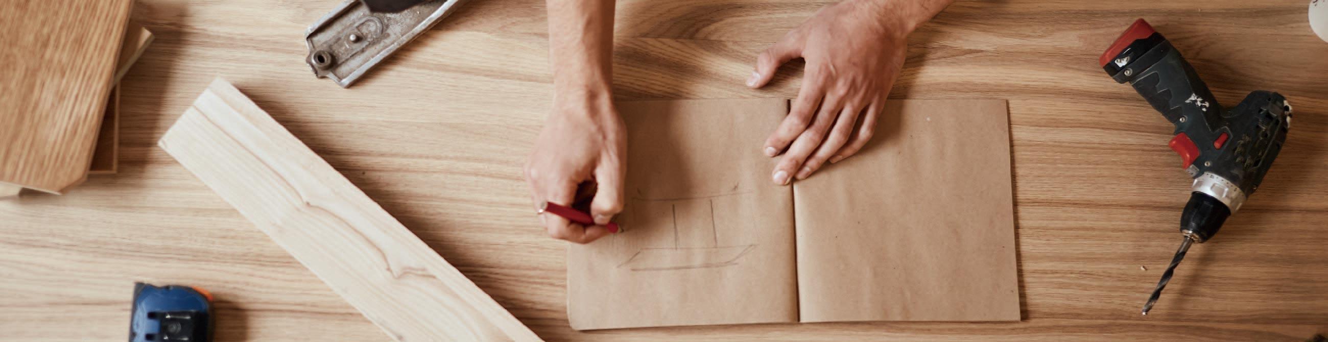 作業台の上で設計図を書く手