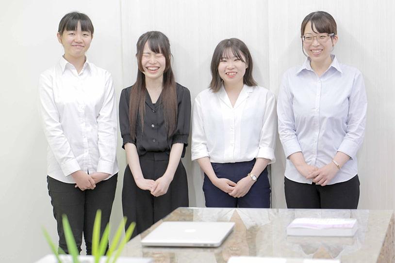 立って並んだ女性社員4人