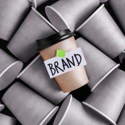 ブランドのラベルが貼られた無地の紙コップ